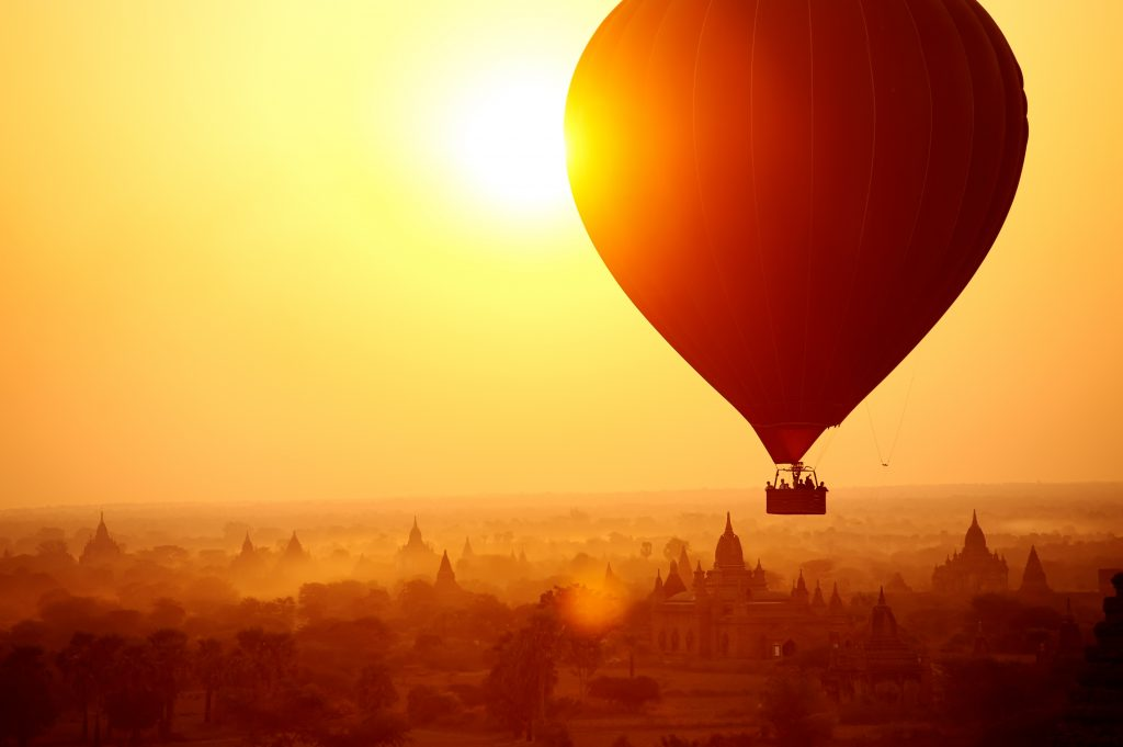 Silhouette of hot air balloon over Bagan in Myanmar, tourists watching sunrise over ancient city